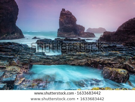 Natural bridge over tidal waters along craggy coastline Stock photo © lovleah