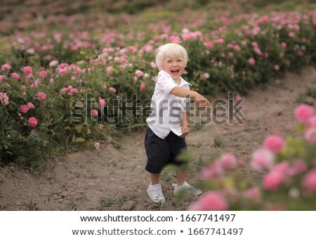 Boy screams and points finger at blossoming flowers Stock photo © ElenaBatkova