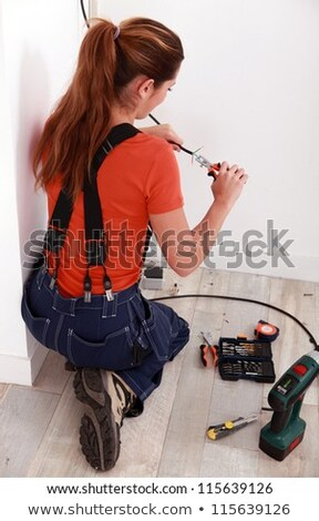 Stock photo: Female electrician pulling cables