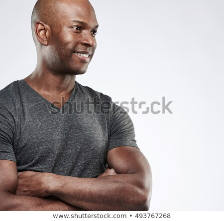 Portrait of a pensive african man with arms folded over black background Stock photo © deandrobot