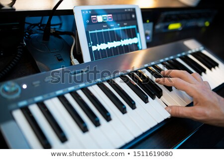 Fingers of young contemporary pianist pressing keys of piano keyboard Stock photo © pressmaster
