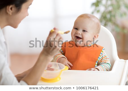 mother feeding baby with spoon stock photo © lopolo