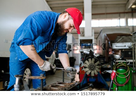 Young master of contemporary service of technical repair bending over engine Stock photo © pressmaster