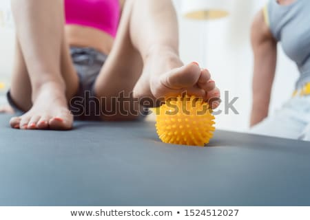 Woman rolling spiked ball under her feet in physical therapy Stock photo © Kzenon