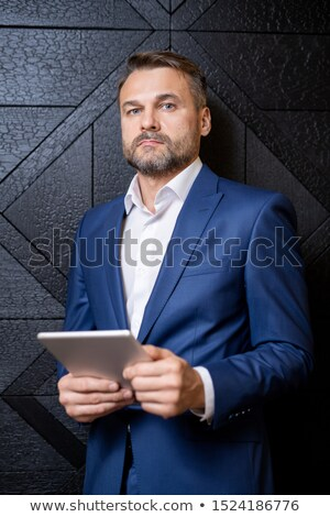 Bearded middle aged well-dressed businessman with digital tablet Stock photo © pressmaster