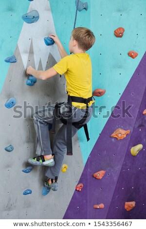 Zijaanzicht jeugdig jongen klimmen muur rotsen Stockfoto © pressmaster