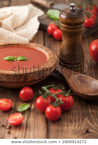Wooden plate of creamy tomato soup with wooden spoon, pepper and kitchen cloth on wooden background  Stock photo © DenisMArt