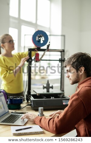 Serious designer concentrating on online work in front of laptop in office Stock photo © pressmaster