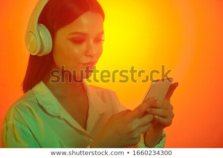 Hands of young woman with headphones scrolling in smartphone for music Stock photo © pressmaster