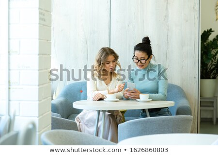 Two young restful women in casualwear discussing online products in smartphone Stock photo © pressmaster
