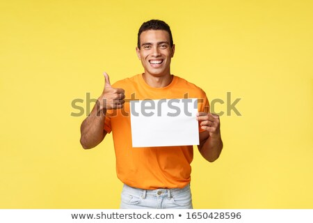 Satisfied happy good-looking masculine man in orange t-shirt, hold blank paper over chest, show thum Stock photo © benzoix