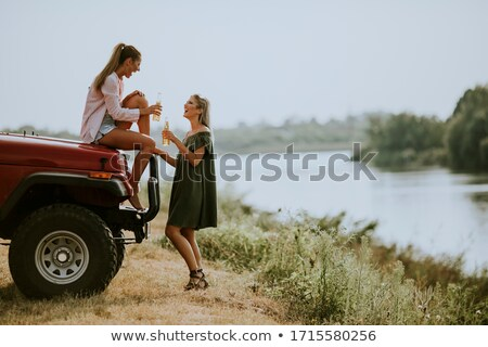 Happy young women drinking cider on the vehicle at the lakeside Stock photo © boggy
