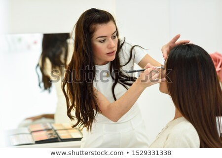 Pretty girl receives eyeshadow from make-up artist Stock photo © imarin