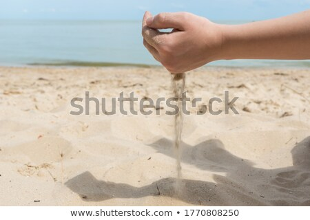 Female hand pours sand on the seashore Stock photo © koca777