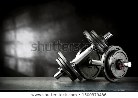 Stock photo: Man lifting a dumbbell at the gym
