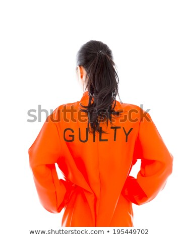 Rear view of a young Asian woman standing with arms akimbo in prisoners uniform Stock photo © bmonteny