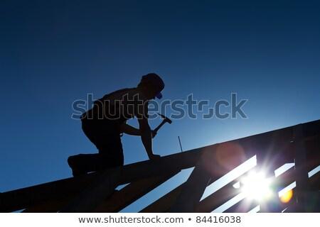 Stockfoto: Silhouet · werken · dak · top · blauwe · hemel