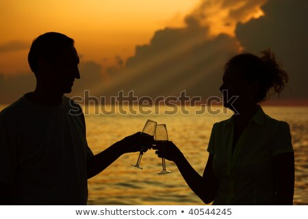 Man and woman clink glasses. Silhouettes against sea. Rays of lights on sky. Stock photo © Paha_L
