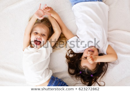 Laughing little girl lying in bed stock photo © deandrobot