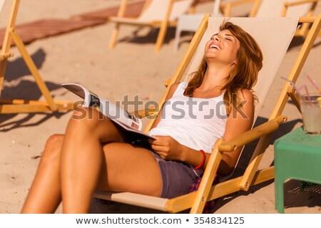 Sonriendo adulto mujer lectura revista silla Foto stock © d13