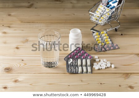 Glass clean water and bunch blister packs of pills Stock photo © ironstealth