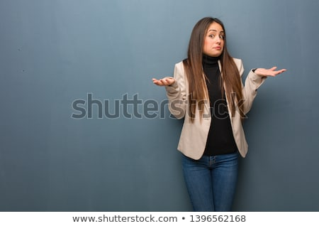portrait of a young businesswoman shrugging shoulders stock photo © deandrobot