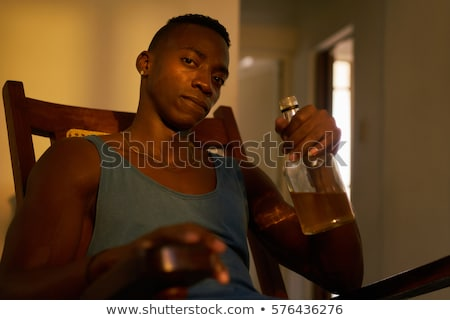 Desperate Unemployed Black Man Drinking Alcohol At Home Alone Stock photo © diego_cervo