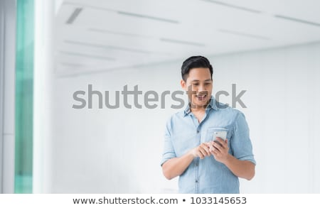 attractive young asian man talking by mobile phone stock photo © deandrobot