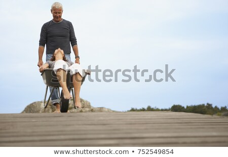 Middle aged woman pushed in wheel barrow Stock photo © IS2