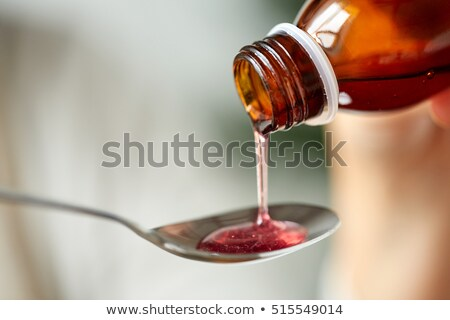 medication or antipyretic syrup and spoon Stock photo © dolgachov