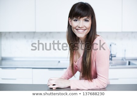 Young woman leaning on a kitchen counter Stock photo © Giulio_Fornasar