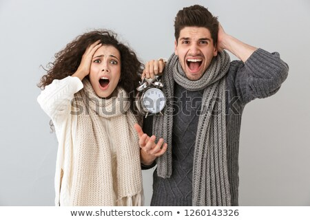 Displeased young loving couple holding alarm clock isolated. Stock photo © deandrobot
