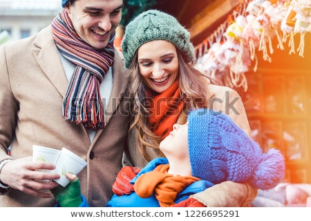 Family standing on Christmas market in front of gift stall Stock photo © Kzenon