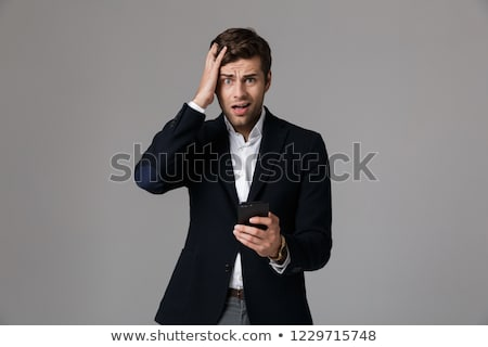 Image of puzzled man 30s in business suit using black smartphone Stock photo © deandrobot