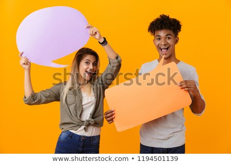 young loving couple standing isolated over yellow background holding speech bubble stock photo © deandrobot
