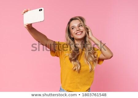 Vrouw poseren geïsoleerd roze muur praten Stockfoto © deandrobot