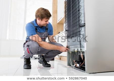 serviceman checking an refrigerator stock photo © andreypopov