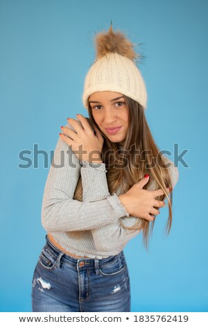 Frozen young woman wearing hat and sweater standing Stock photo © deandrobot