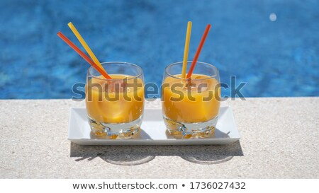 Stock photo: Glass with a bright tequila sunrise cocktail by the pool
