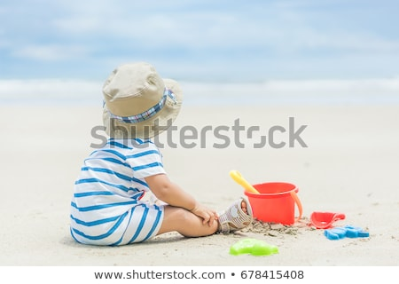 Stockfoto: Little Girl Playing With Sand Near The Coast At Beach