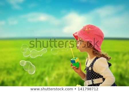 Stock photo: teenage girls blowing bubbles at summer park