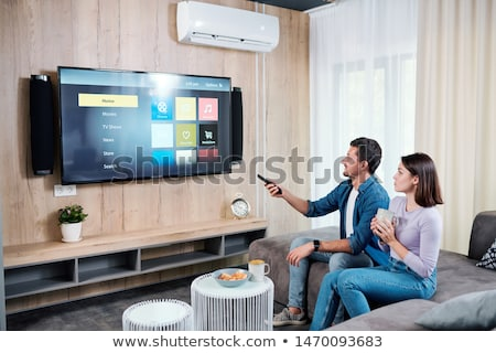 young couple having tea while going to watch something on plasma tv panel stock photo © pressmaster
