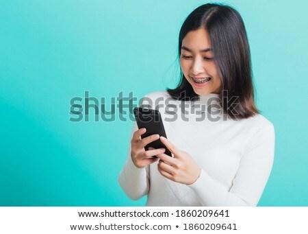 Portret zachwycony młoda kobieta uśmiechnięty wpisując smartphone Zdjęcia stock © deandrobot