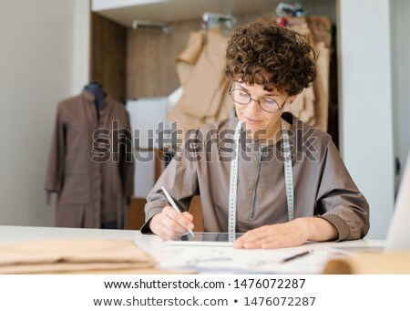 Young female designer concentrating on looking though digital models Stock photo © pressmaster