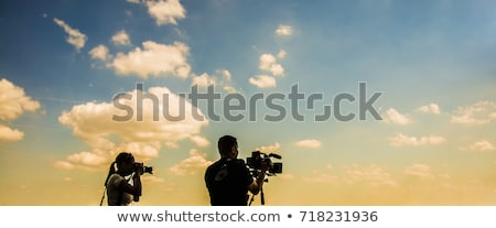 Silhouette of a female videographer at work on a background of infographics. Stock photo © ConceptCafe