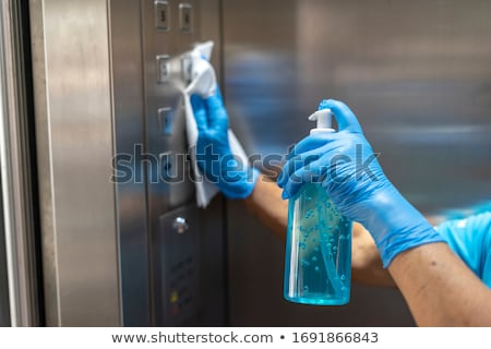 man disinfecting the buttons of an elevator Stock photo © nito