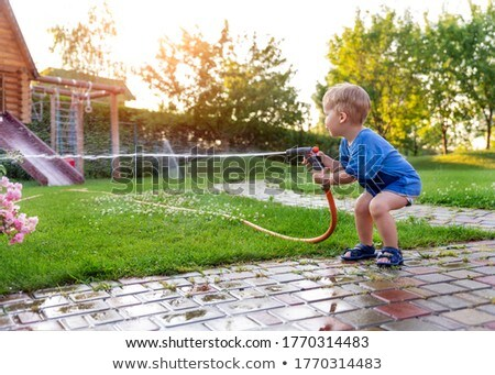 portrait of boy holding water spray stock photo © zzve