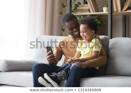 father with smartphone and baby playing at home stock photo © dolgachov
