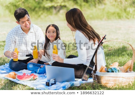 Parents together with little girl have rest in summer garden. Girl plays in lap parents. Stock photo © Paha_L