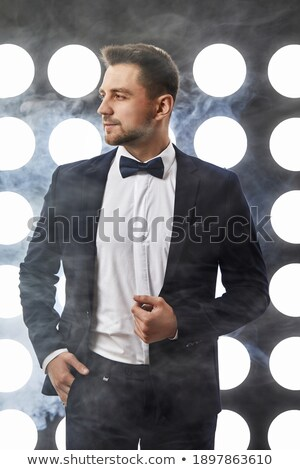 young businessman in tuxedo and bowtie posing Stock photo © feedough